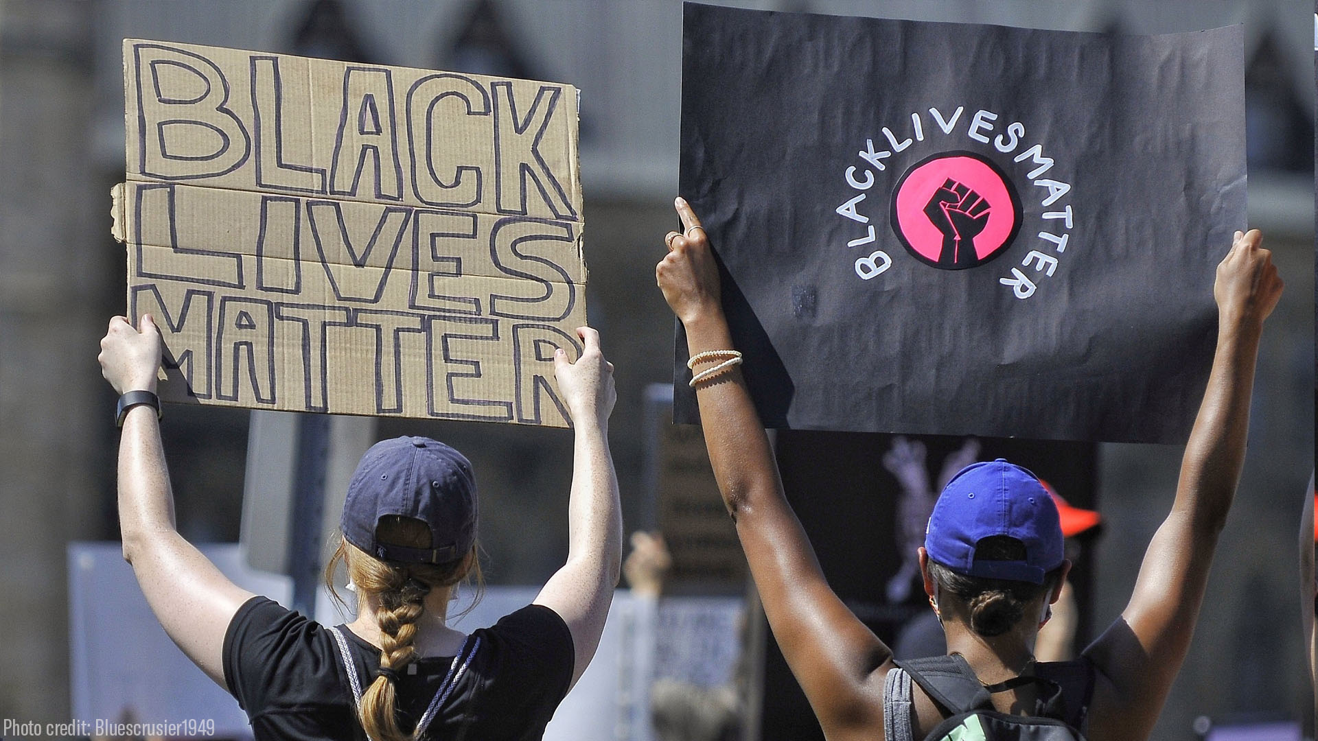 """Photo: Two people are pictured with their back facing the camera. They are outside rand raise handwritten signs that say """"Black Lives Matter."""""""