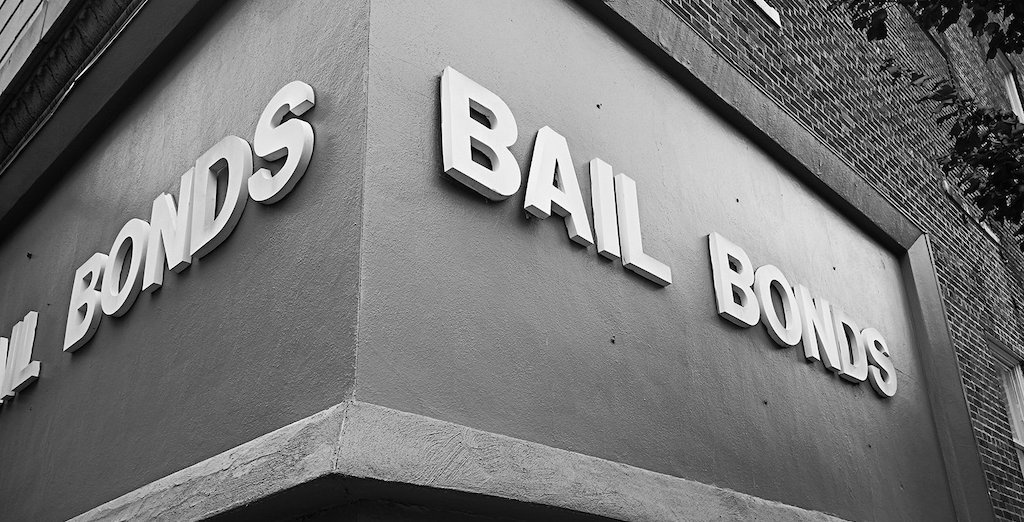 """A black and white image of a building sign that says """"Bail Bonds"""""""