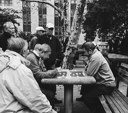 old men playing chess on a park bench