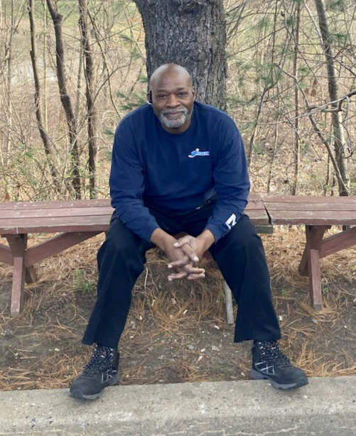 Calvin McNeill is a Black man, wearing a navy blue shirt, black pants, and boots, and is sitting on a bench in front of a tree.
