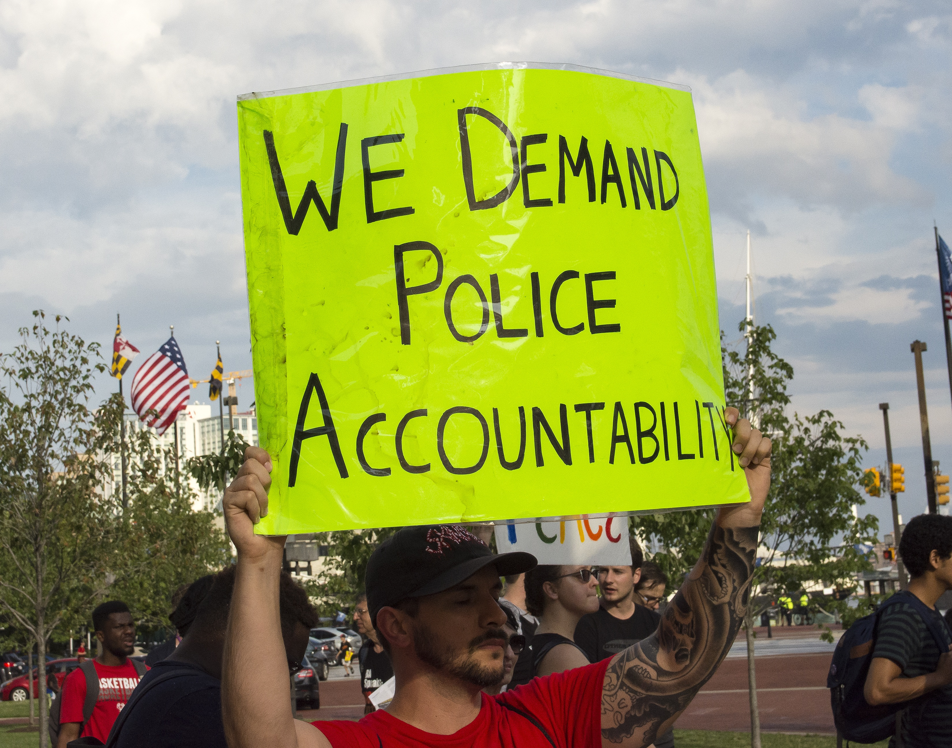 Man holding a sign that reads: We Demand Police Accountability