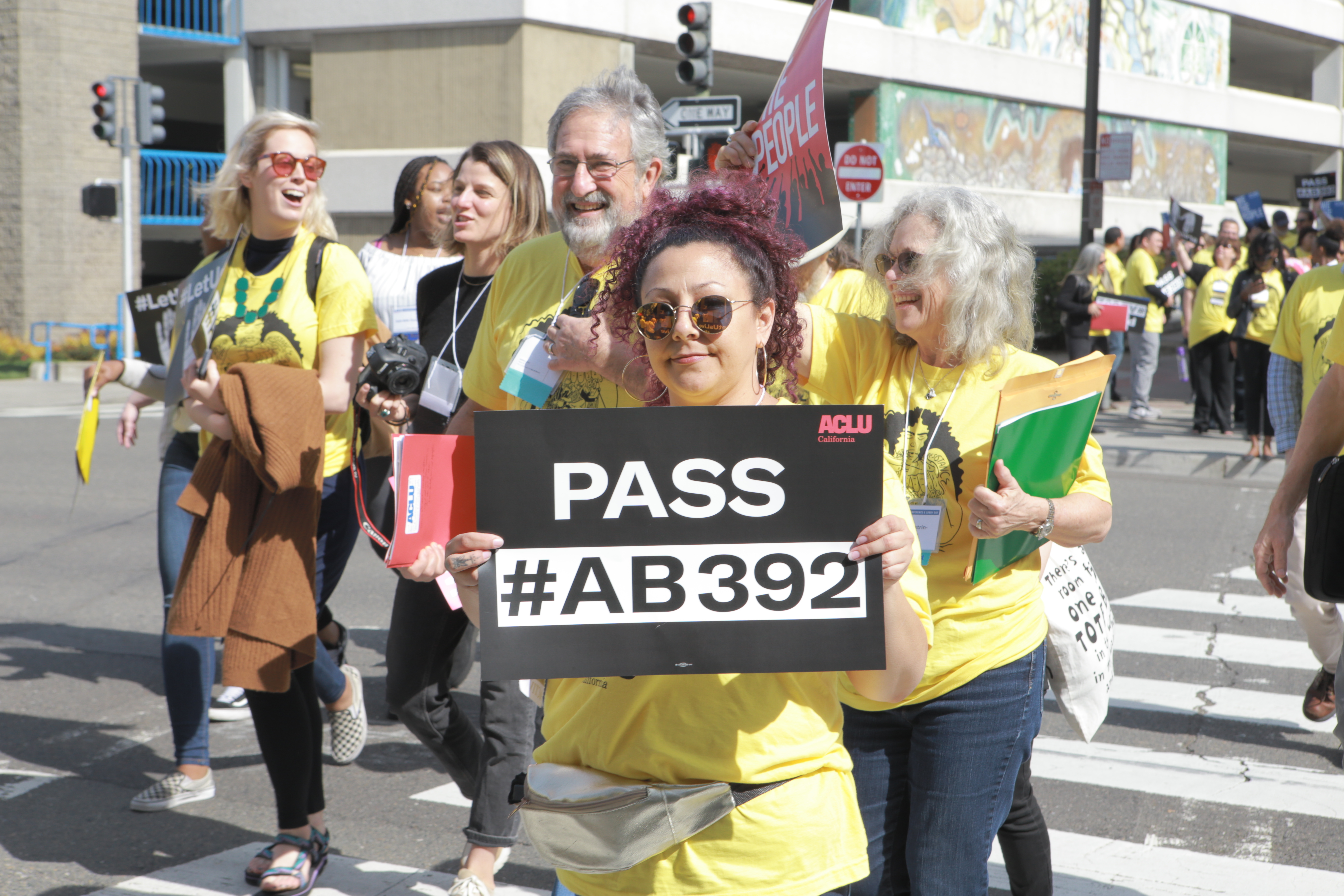 Activist holding Pass AB 392 sign