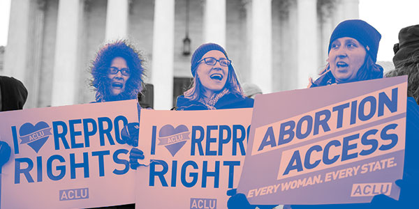 Three women holding repro rights signs