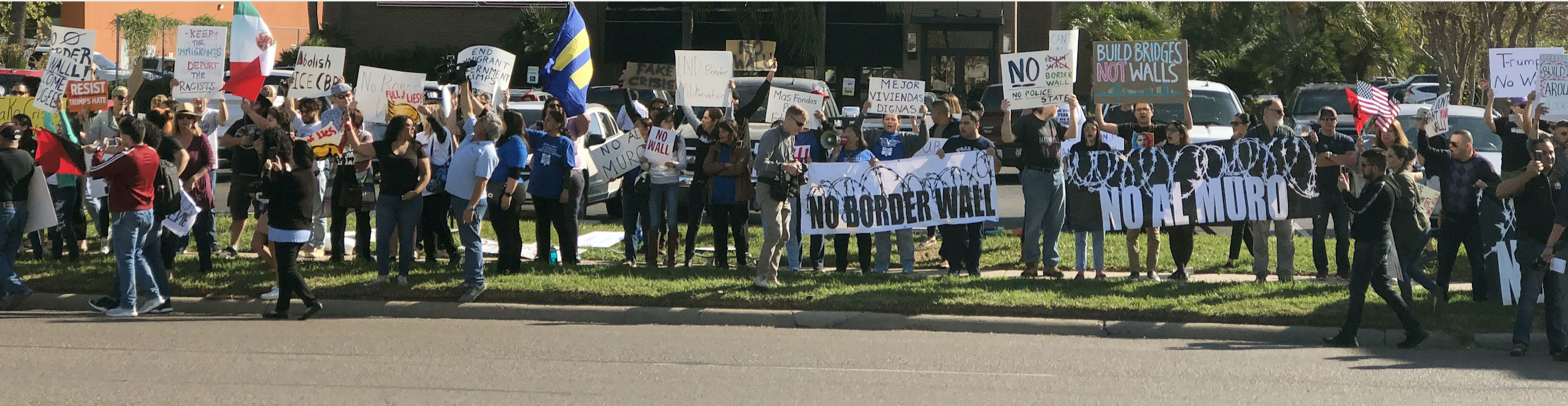 "Photo: A crowd of people stand along a street in the Rio Grande Valley. Behind them is a restaurant and other businesses. They hold signs, one of which says ""No Border Wall."""