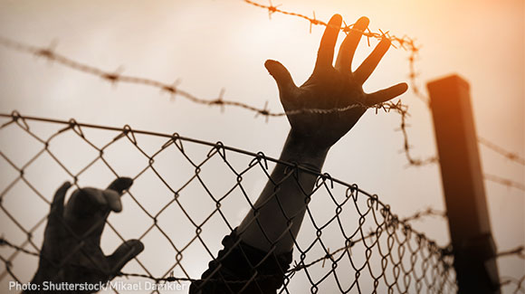 Hands reaching over a barbed wire fence'