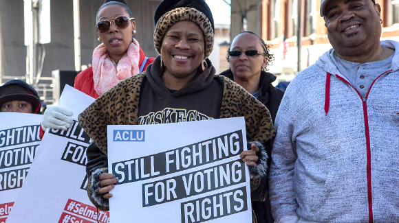 Woman in Selma, Alabama holds sign that says 'Still fighting for voting rights'